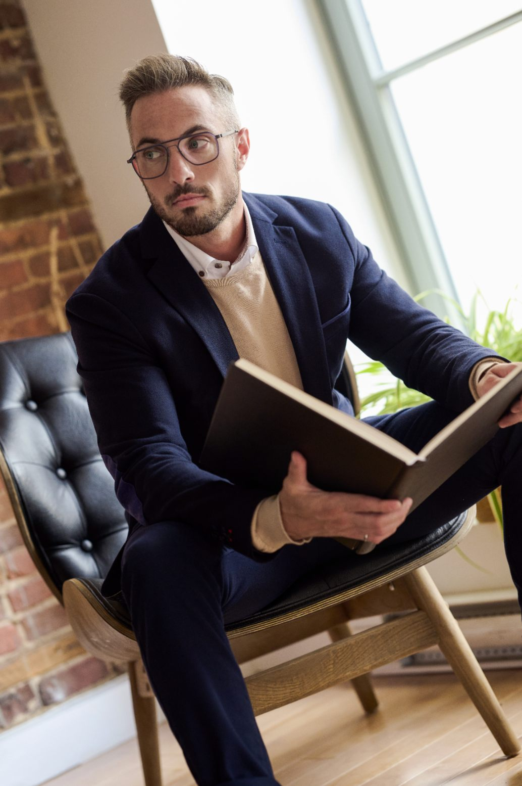 Classy man wearing glasses sitting with a book in hands